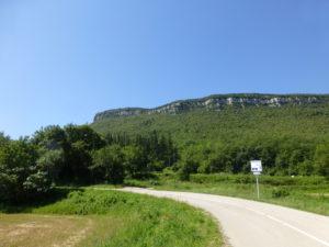 Carretera per on passen els ciclistes amb un paisatge muntanyós al fons